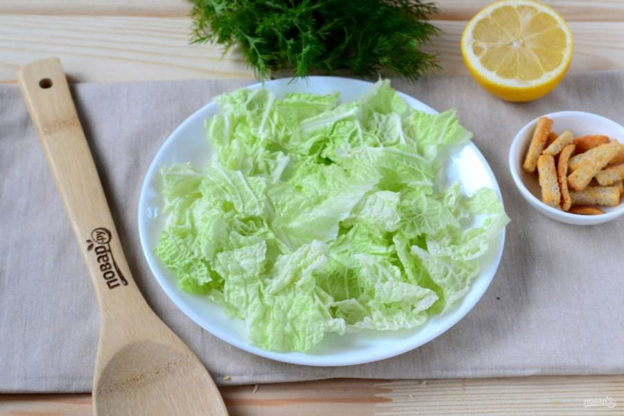 Начинайте собирать салат. Листья пекинской капусты порвите на небольшие кусочки и выложите на дно плоской тарелки.