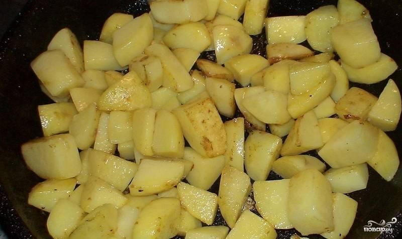 Картофель почистите, помойте, нарежьте кубиками и обжарьте до полуготовности на масле в сковороде.