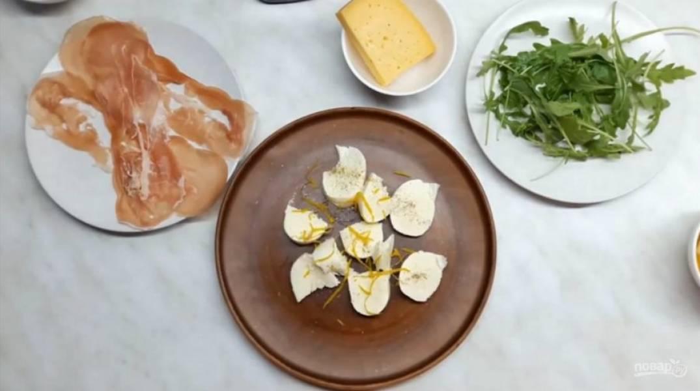 1. Тщательно очистите апельсин, очень тонко нарежьте его. Порвите шарик моцареллы крупными кусками, посолите и выложите на тарелку, в которой собираетесь подавать блюдо. Посолите, поперчите ее, сверху добавьте цедру лимона.