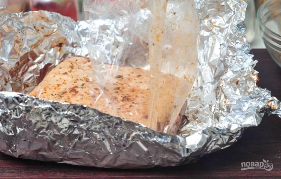 Переложите рёбра из пищевой плёнки в фольгу.