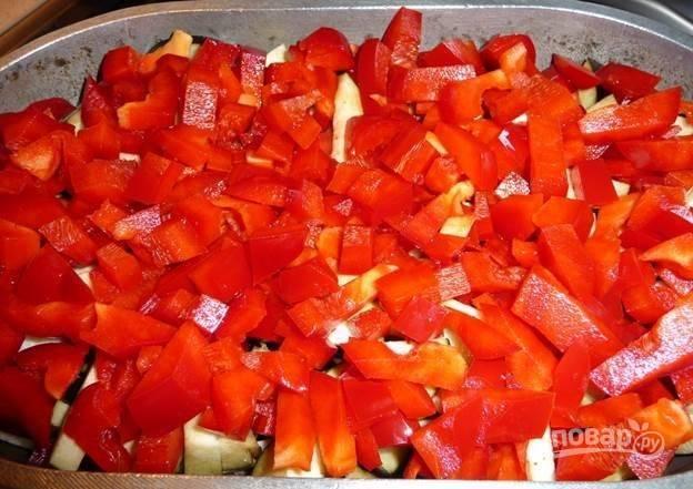 3.Вымойте и очистите перцы от семян, нарежьте, выложите поверх баклажанов.