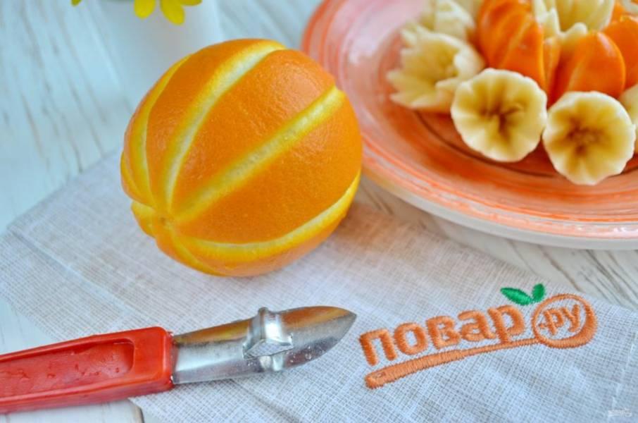 На апельсине сделайте борозды, разрежьте апельсин на две половинки, каждую половинку — на тонкие пластинки.