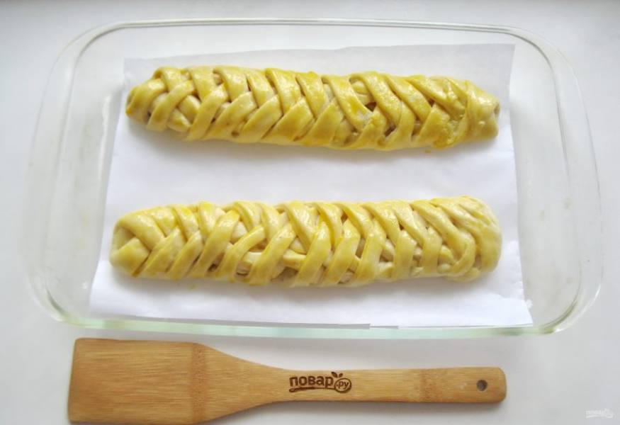 Выложите яблочные косички в форму для выпечки. Смажьте взбитым яйцом. Дайте расстояться при комнатной температуре 30 минут.