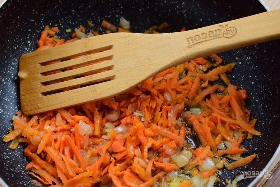 Морковь натрите на терке. В глубокой сковороде разогрейте растительное масло. Пассеруйте оставшийся лук и чеснок до прозрачности, добавьте томатную пасту, перемешайте. Добавьте морковь, перемешайте и обжарьте до румяной корочки.