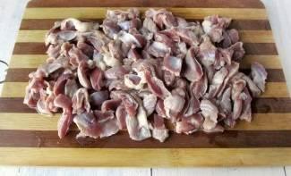 Куриные желудки промойте водой и нарежьте на порционные кусочки.
