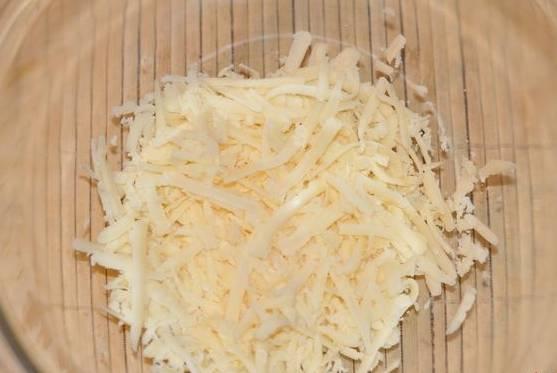 Натрите на терке сыр, выложите в салатницу.