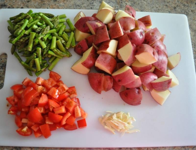 3. Далее можно заняться овощами. Молодой картофель достаточно просто вымыть как следует и нарезать. Измельчить немного спаржу и помидоры. Чеснок очистить и при желании пропустить через пресс, но можно тоже нарезать.