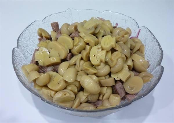 С шампиньонов сливаем жидкость, нарезаем их на пластинки и добавляем в салат.