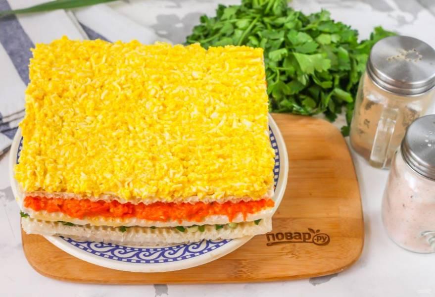 Последний корж обмажьте яичной массой и выложите на морковный слой. Если у вас остались еще ингредиенты, выкладывайте их на вафельные коржи и готовьте более высокий закусочный торт.
