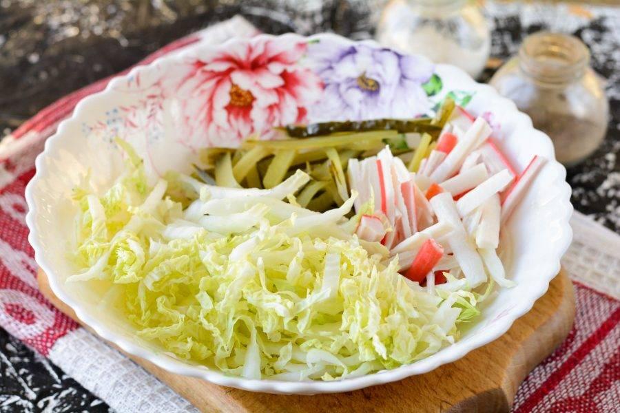 Переложите в миску нарезанные продукты: капусту, крабовые палочки и огурцы.