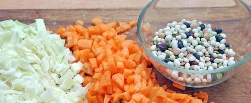 Разогреваем в кастрюле 2 литра воды. Нарезаем 200 грамм капусты и две морковки. Подготовьте 100 грамм бобовых.