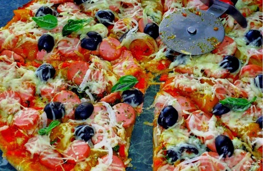 Готовую пиццу разрезаем на кусочки. Расплавленный сыр томно тянется под лезвием ножа. Пицца источает неповторимый аромат, свойственный только ей. Подавайте угощение к столу!