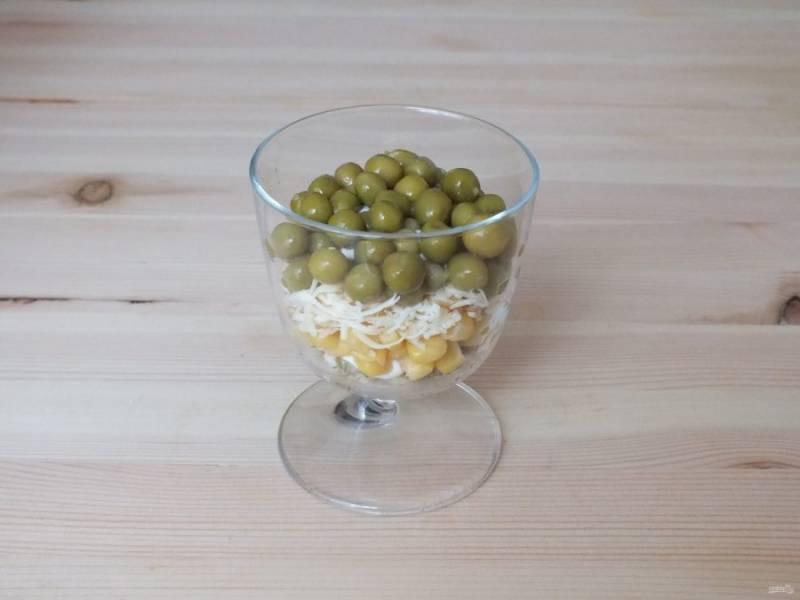 Далее следуют слои из тертого сыра, майонеза и зеленого горошка.