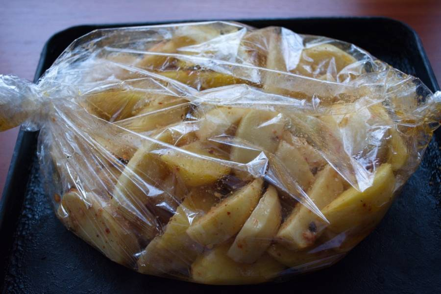 Переложите картофель (вместе с остатками маринада) в рукав для запекания. Разогрейте духовку до 200 градусов. Запекайте картофель в рукаве до готовности около 1,5 часа.