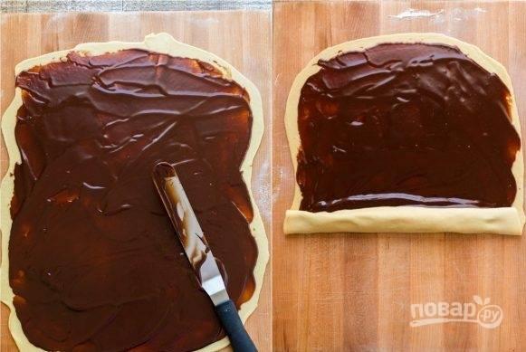 """4. Разделите тесто на две части и раскатайте его на поверхности, посыпанной мукой. Смажьте каждую часть готовым шоколадом и скатайте в """"колбаску""""."""