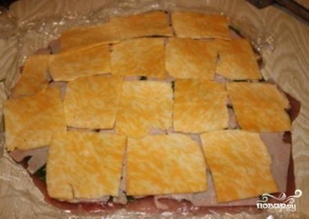 Ветчину и сыр нарезаем тонкими пластинками и выкладываем  на мясо. Сначала ветчину, поверх нее сыр.