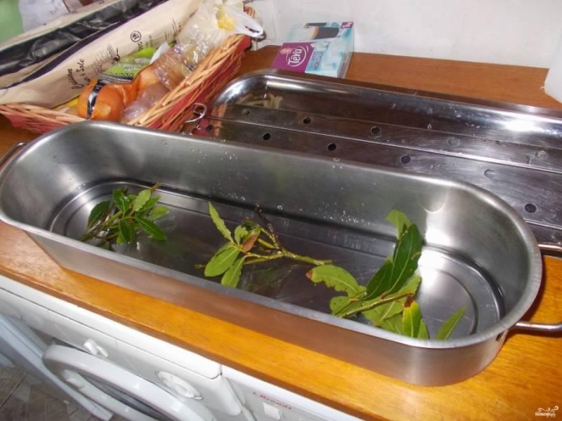 2. На самое дно выложите лавровый лист, после чего поставьте подставку. Если у вас нет рыбницы, то используйте обычную форму для запекания, но тогда подушку делайте из овощей.
