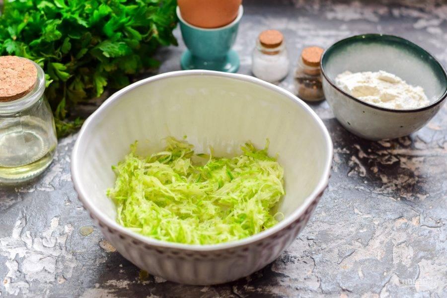 Кабачок ополосните и просушите, натрите кабачок на мелкой терке, лишнюю жидкость отожмите, переложите кабачковую массу в миску.