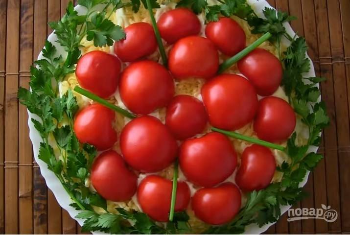 6. Помидоры разрежьте на половинки и украсьте ими салат. По бокам выложите веточки зелени. Готово!