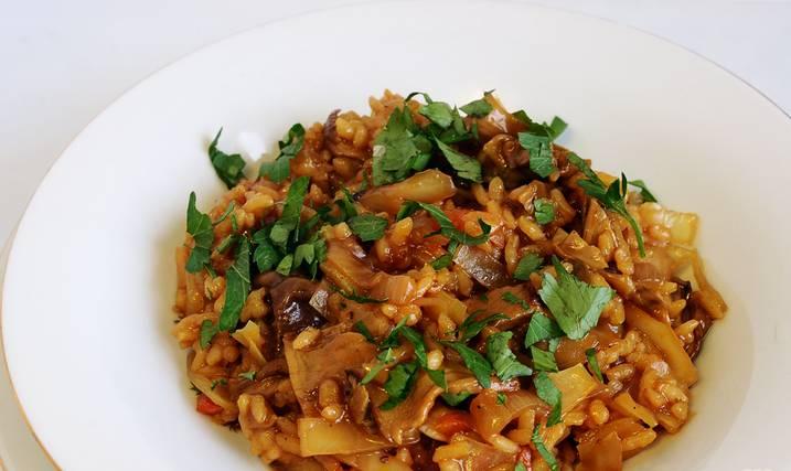 Добавив все приправы, доведите солянку до готовности. Это легко проверить по рису и капусте: когда они готовы, то и сама солянка готова. Солянка должна быть густой, подливайте при необходимости в нее воду при тушении, чтобы она не подгорела.  Готовую грибную солянку с рисом и капустой подавайте с зеленью. Приятного аппетита!