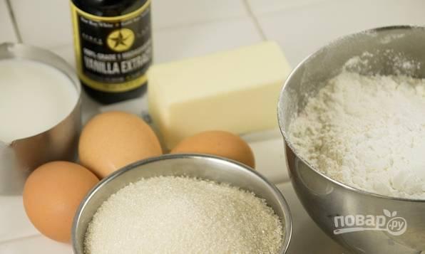 Приготовим тесто для коврижки. Взбиваем масло комнатной температуры с сахаром. Подмешиваем половину муки, просеянной с разрыхлителем и солью. Взбиваем массу миксером, подливая молоко и добавляя по одному яйцу. В конце досыпаем муку и окончательно вымешиваем тесто.