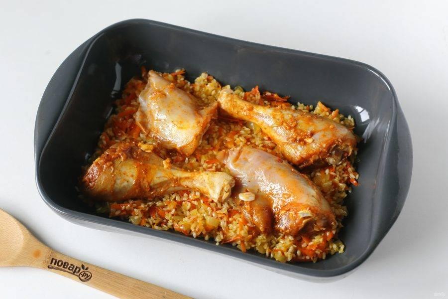 Форму смажьте маслом и выложите овощи с рисом. Сверху положите маринованную курочку.