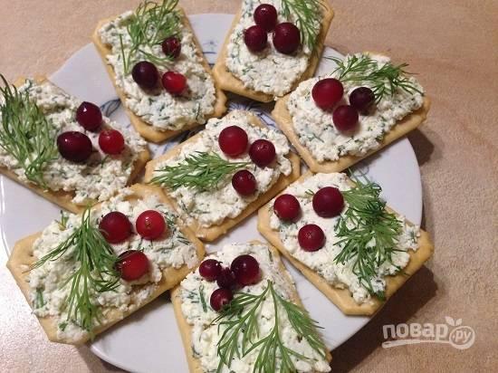 5. И последний штрих - украшаем крекеры зеленью и ягодами клюквы.