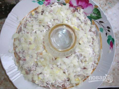5. Репчатый лук очистите и нарежьте кубиком, переложите в миску и залейте кипятком, чтобы ушла горечь. Отожмите лук и выложите следующим слоем.