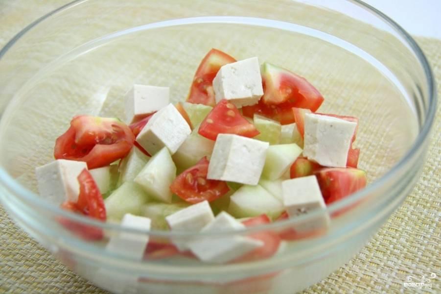 Сыр Фета порежьте кубиками. По размеру они не должны превышать огурцы и помидоры. Сложите все ингредиенты в салатницу.