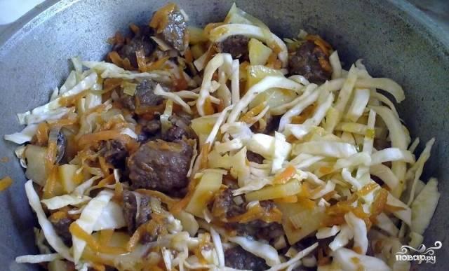 свежую капусту необходимо нашинковать и переложить в казан к мясу и овощам, потушить еще 5 минут.