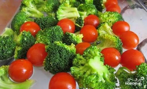 Промойте брокколи и разделите на соцветия, а затем отварите 2-3 минуты в кипящей подсоленной воде. Разложите отваренные соцветия брокколи и томаты черри в форме для запекания.