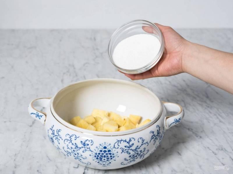 Ананас почистите, листья оставьте, нарежьте кубиками. Уложите фрукт в тарелку с сахаром. Перемешайте, оставьте настаиваться под крышкой на 15 минут.