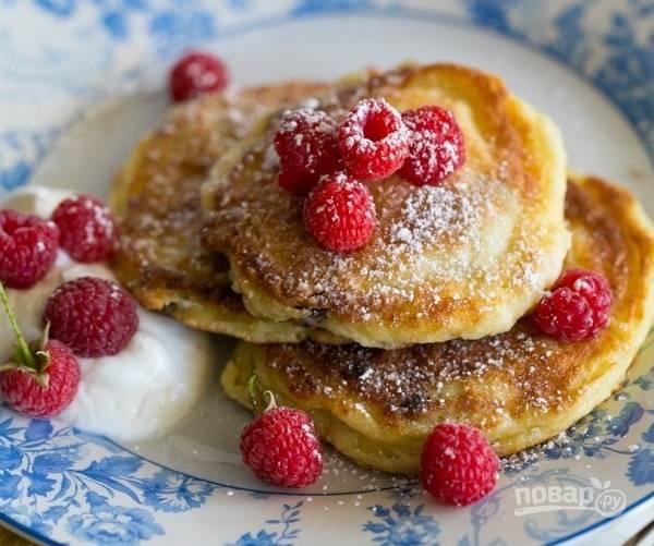 9.Выложите творожники на тарелку, украсьте сахарной пудрой, малиной и подавайте со сметаной.