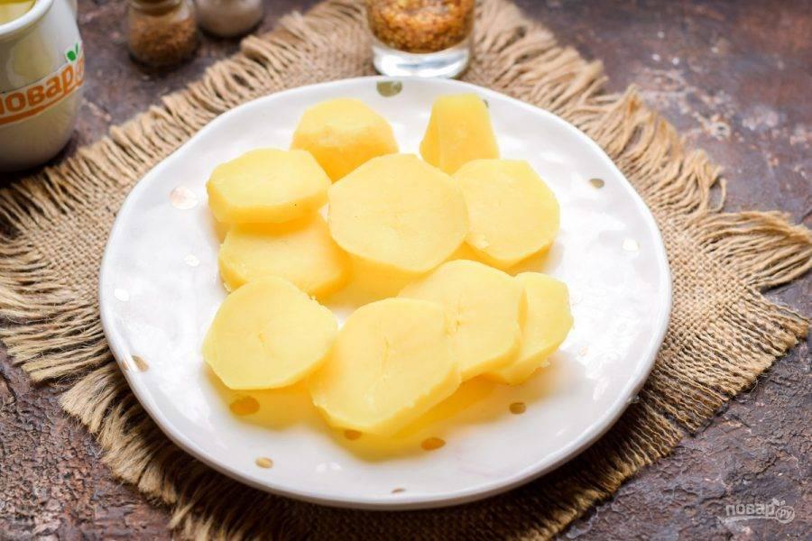 Вареный картофель очистите и нарежьте кружочками.