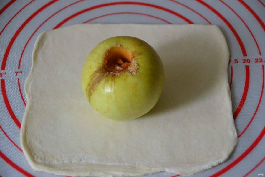 Раскатайте каждый кусочек теста в квадрат, размером достаточным, чтобы завернуть в него яблоко.