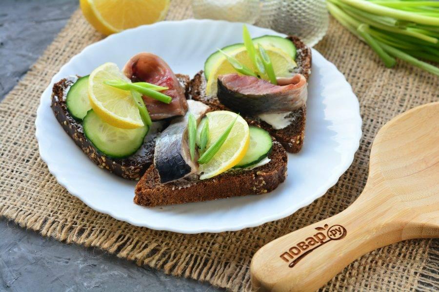 Украсьте бутерброды зеленым луком.