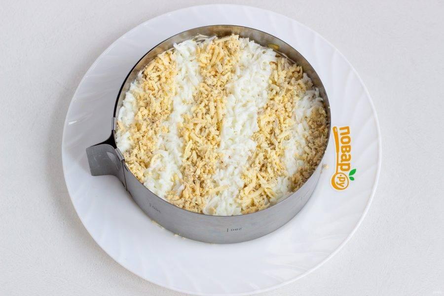 Яйца разделите на белки и желтки, натрите отдельно на мелкой терке и выложите в виде полос на салат. Поставьте салат на 1-2 часа в холодильник, затем аккуратно снимите кольцо.