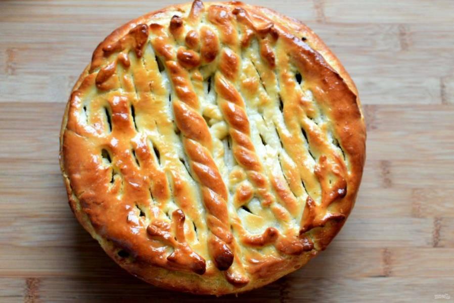 Защипните фигурно края, смажьте пирог подслащенным молоком и дайте немного подойти. Выпекайте в разогретой до 180 градусов духовке, первые 15 минут с паром, плеснув на дно чуть больше полстакана горячей воды. Готовый пирог смажьте сливочным маслом и накройте салфеткой.