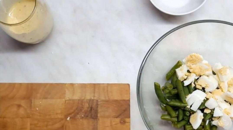 3. Дайте фасоли остыть до комнатной температуры, высыпьте ее в миску и добавьте к ней нарезанное крупными кусочками отваренное яйцо. Туда же добавьте немного мелко нарезанного укропа.