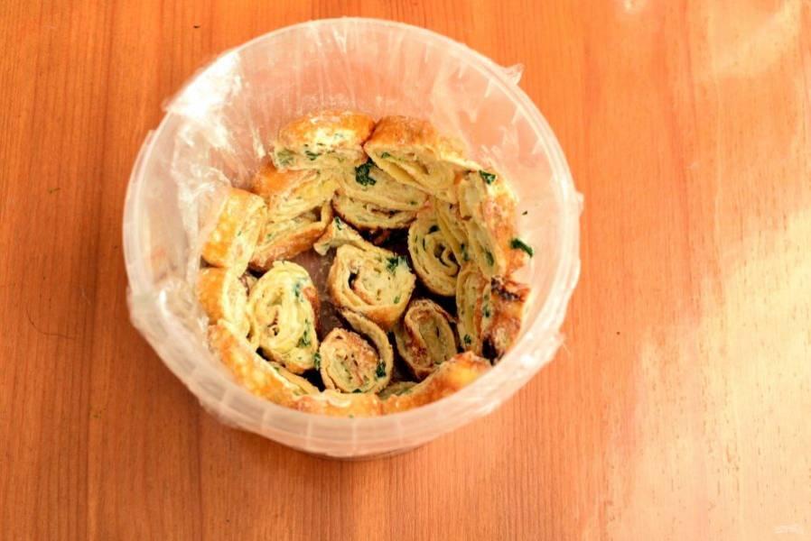 Возьмите подходящую салатницу или другую посуду. Удобно делать такой салат в пластиковом ведерке. Выстелите посуду изнутри пищевой пленкой. Чтобы упростить задачу, немного смочите посуду водой. Нарежьте яичные блинчики кусочками толщиной в 2 см и уложите их по дну и выше по периметру посуды,  срезом наружу.
