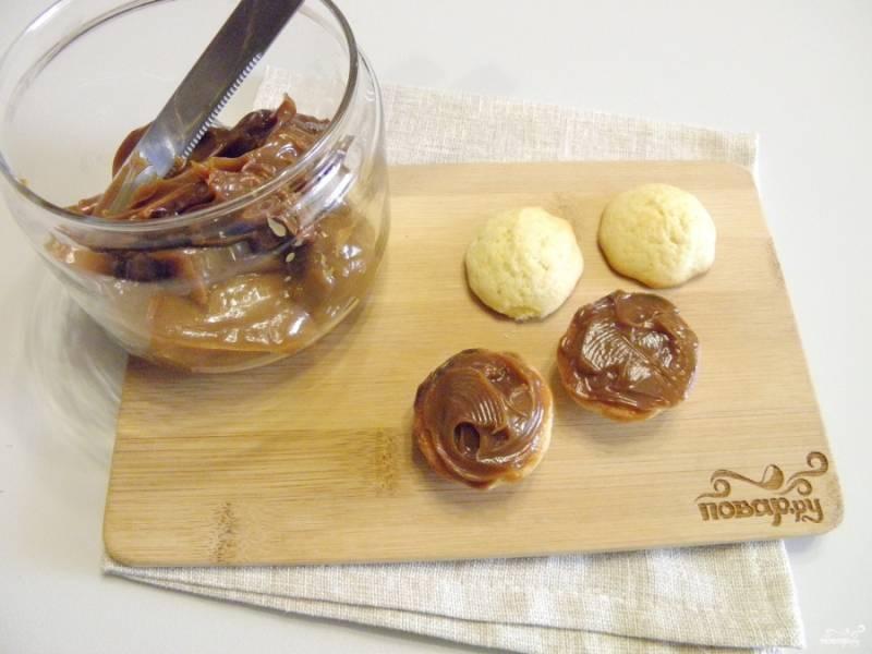 Смажьте низ печенья вареной сгущенкой, приклейте таким образом второе печенье.