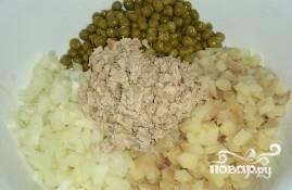 В одну миску складываем печень трески, картофель, репчатый лук и зеленый горошек. Также в миску добавляем 2 столовые ложки майонеза. Солим, перчим, все смешиваем.