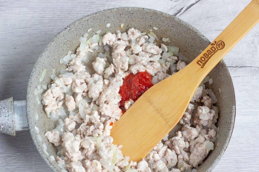 Добавьте фарш и обжарьте до полуготовности, а затем 1 ст. ложку томатного соуса. Перемешайте и обжарьте в течение 1-2 минут.