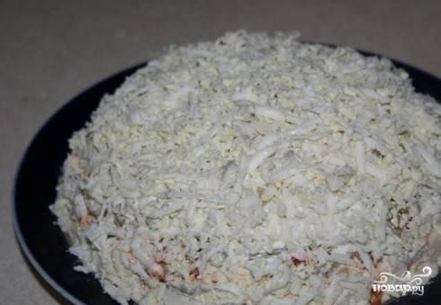 9. На покрытую майонезом морковку выложите слой соленого огурца. Сверху натертыми белками накройте салат, как шаром. Поставьте в холодильник.