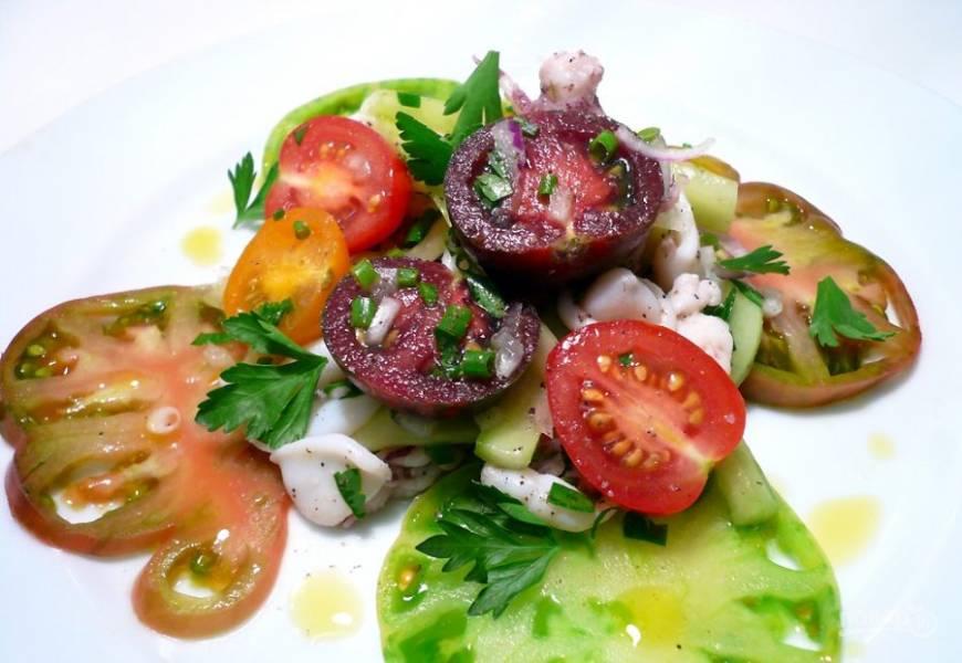 Выложите на тарелку кружочки разноцветных томатов. Смешайте маринованные кальмары с огурцом и двумя видами лука. Выложите поверх помидоров. Сверху положите половинки черри. Присыпьте зеленью. Смешайте винный уксус и растительное масло. Полейте этой смесью салат.