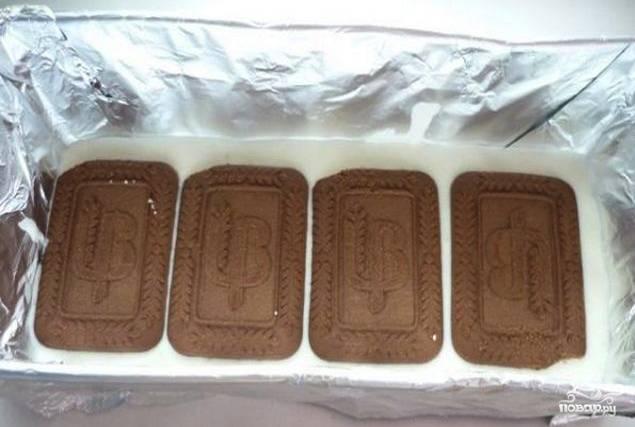 Теперь можно формировать торт. Возьмите удобную форму, застелите её фольгой. Дно формы уложите шоколадным печеньем. На печенье налейте творожную массу слоем толщиной около сантиметра. Затем снова уложите слой печенья и так чередуйте слои, пока не закончатся ингредиенты.