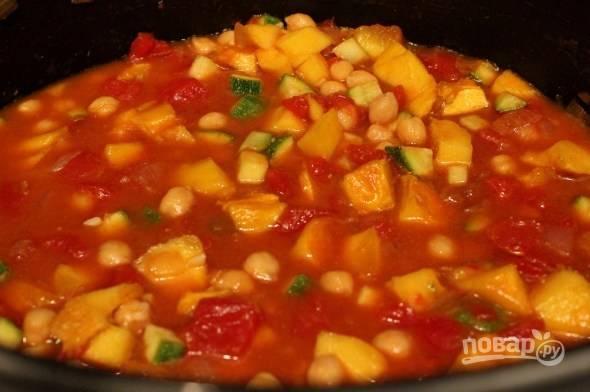 Добавьте тыкву в сковороду вместе с консервированной, также влейте бульон. Добавьте нут, кумин, соль, перец, корицу и сахар.