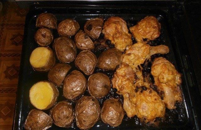 6. Когда курица замариновалась, противень застилаем бумагой, смазываем маслом, выкладываем курицу и картошку срезом вниз. Запекаем час.