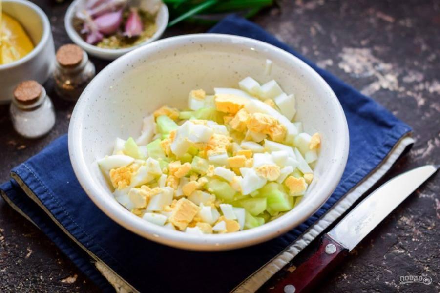 Куриное яйцо сварите вкрутую, очистите и нарежьте небольшими кубиками. Переложите яйцо ко всем ингредиентам.