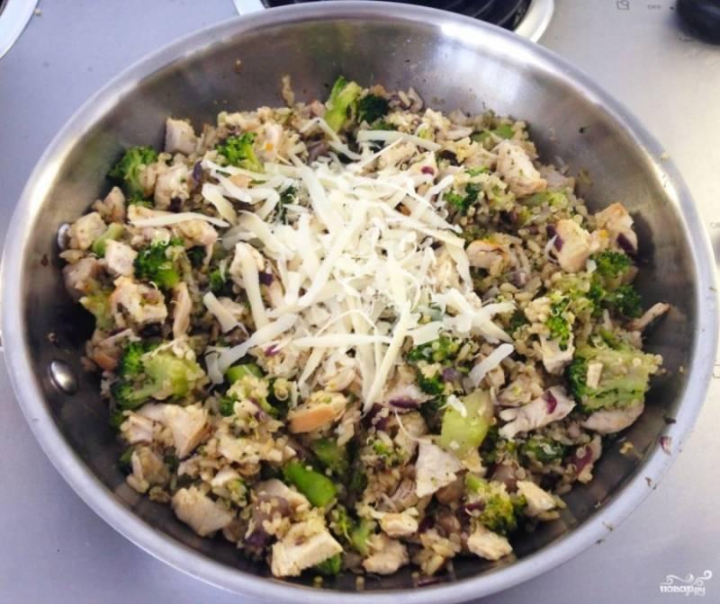 Добавьте на сковороду курицу отварную порезанную кусочками, киноа с рисом. Все перемешайте, сверху посыпьте тертым сыром, готовьте буквально пару минут.